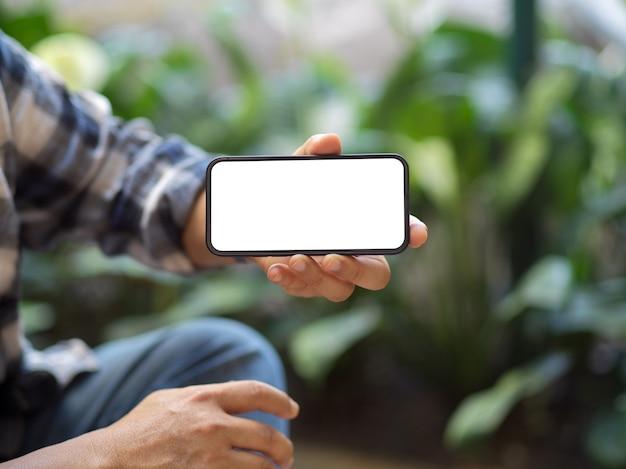 カメラにスマートフォンの画面を表示している男性にクローズアップ