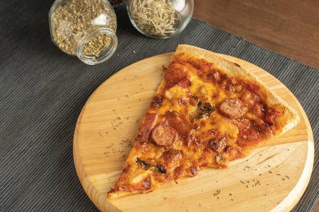 Закройте пиццу с начинкой пепперони на закругленном деревянном подносе, поместите на подставку из черной ткани и группу трав и специй в банках на кончиках