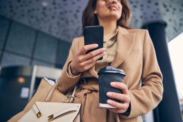 그녀의 손에 일회용 커피 종이 컵을 들고 웃는 여성에 가까이