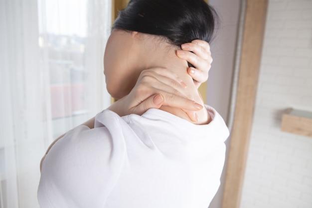 Крупный план руки женщины, массирующей шею. у девушки болит шея