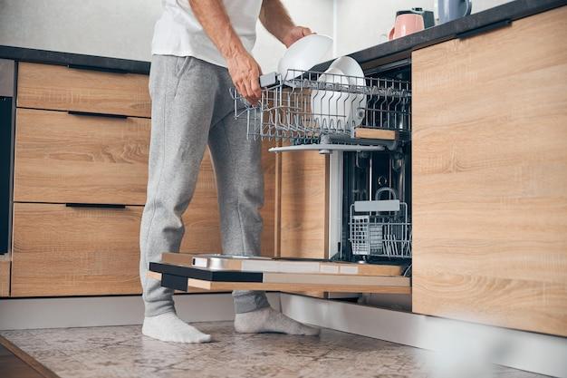 Крупным планом - взрослый мужчина, делающий домашние дела и стоящий возле посудомоечной машины дома