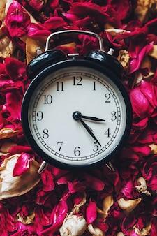 乾燥した花びらと目覚まし時計のクローズアップ