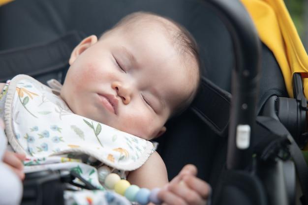 유모차 안에 잠자는 아시아 아기에 근접