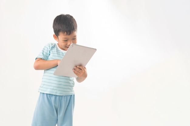 分離したデジタルテーブルで遊んでいるアジアの少年のクローズアップ