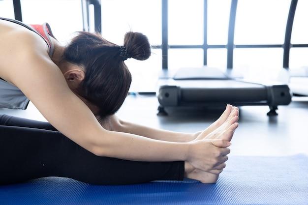 座った前屈姿勢でヨガを練習しているアジアの女性のクローズアップ