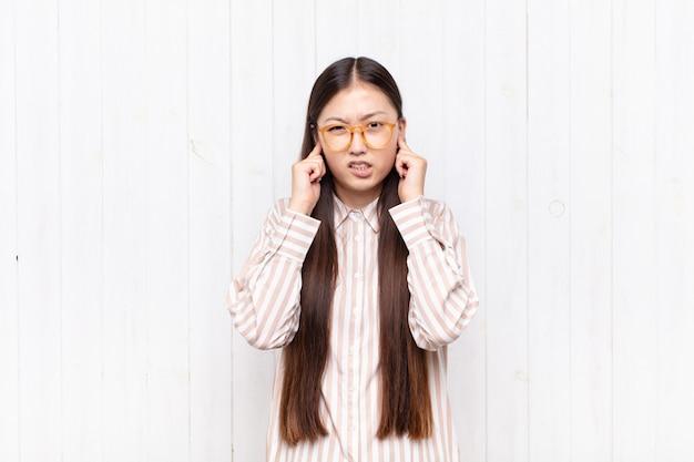 Крупным планом азиатская молодая женщина выглядит сердитой