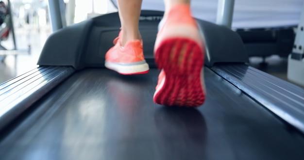 トレッドミルで有酸素運動をしているジムで運動しているアスリートの足をクローズアップ