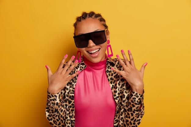 Крупным планом привлекательная беззаботная молодая женщина в солнцезащитных очках