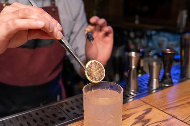 Крупным планом на бармена и шейкер для коктейлей