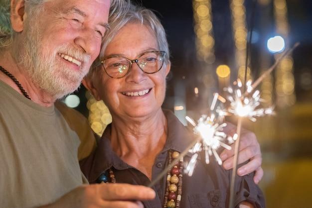 밤에 야외에서 아름다운 노부부가 반짝 조명으로 즐겁게 노는 모습을 클로즈업합니다. 사랑으로 포옹 하는 두 웃는 은퇴한 사람들