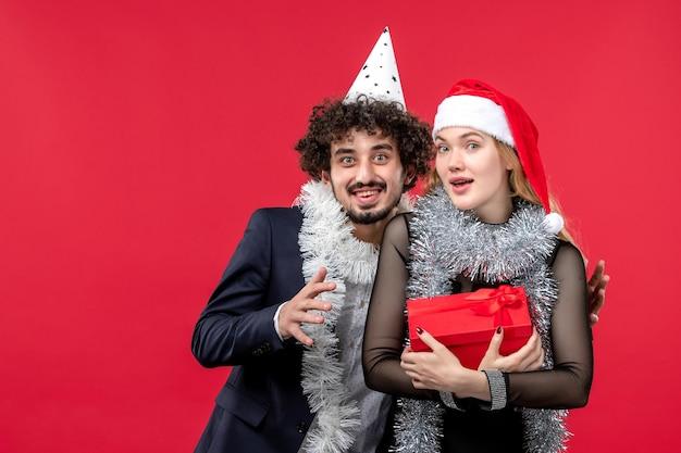 孤立したサンタの帽子をかぶって美しい若いカップルにクローズアップ