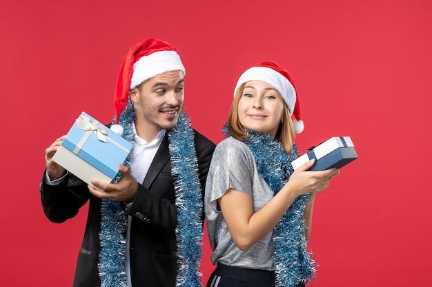 Крупным планом на красивая молодая пара в шапках санта-клауса изолированы