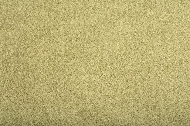 Закройте на бежевых обоях текстуры ковра