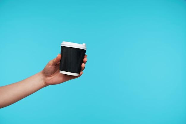手でコーヒーを持って黒い紙コップにクローズアップ