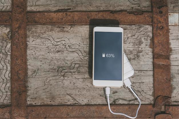 Крупным планом на пустой мобильный телефон с блоком питания в руке