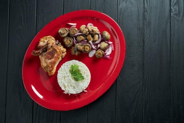キノコのピクルスと黒い木製のテーブルの赤いプレートにチキンとご飯にクローズアップ。ダイエットのための健康食品