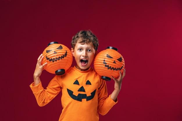 Крупным планом мальчик в рубашке на хэллоуин, держа тыквы