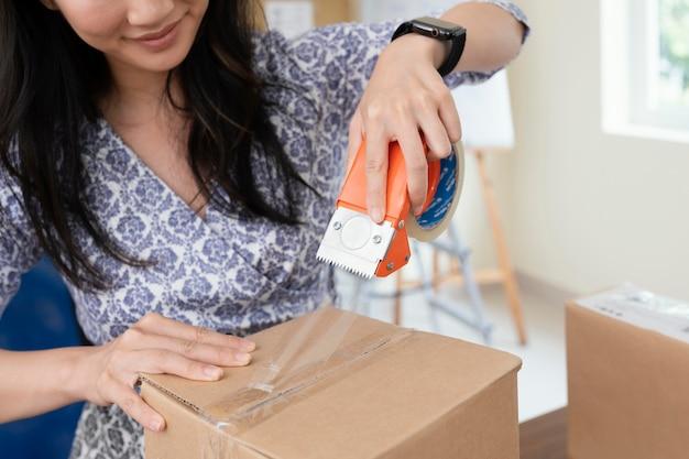 配達のためのブルネットの女性の包装箱にクローズアップ