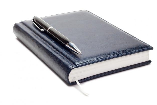 分離されたペンでビジネス日記にクローズアップ