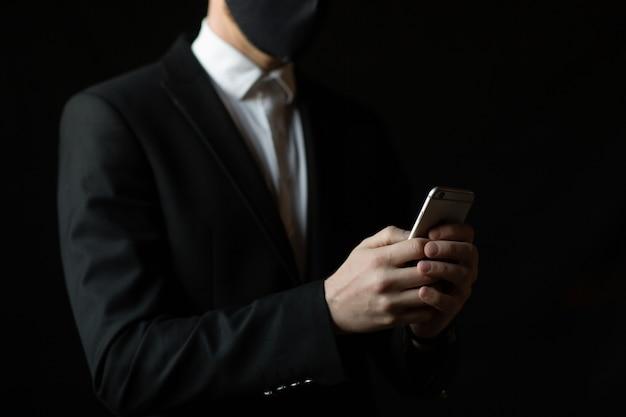 그의 스마트 폰 확인 얼굴 마스크를 착용하는 사업가에 닫습니다
