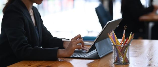 Крупным планом на руках бизнесвумен, набрав на беспроводной клавиатуре цифрового планшета