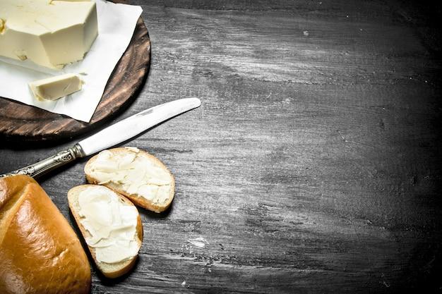 ボード上のナイフでバターにクローズアップ