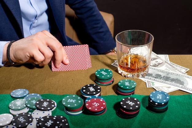 Крупным планом на карты в мужских руках на покерном столе