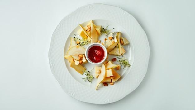 Крупным планом на сырной тарелке с орехами, виноград, мед. взгляд сверху на разных видах сыра на белой таблице с космосом экземпляра.