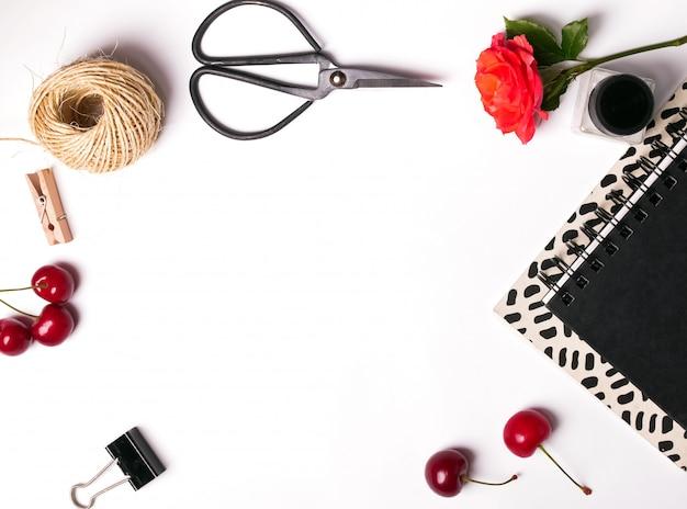 Крупным планом вишни, ножницы и блокноты