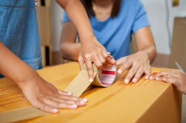 Крупным планом - рука ребенка, помогающая родителям упаковать вещи, и скотчем, чтобы скотчить коробку, прежде чем переехать в новый дом в день переезда. концепция ремонта и переселения дома.