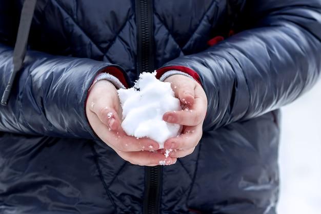 Крупным планом ребенок держит снег в руках