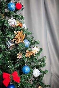 家の中で花輪と装飾が施されたクリスマスツリーにクローズアップ。装飾的でお祝いの緑の木