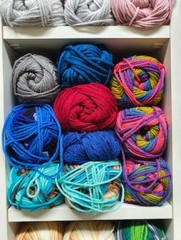잡화점 니트워크의 선반에 뜨개질을 하기 위해 다채로운 원사 또는 양모 공을 닫습니다.