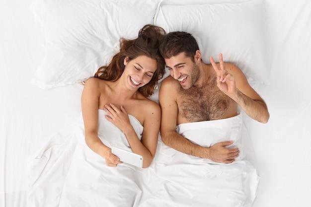 白い毛布の下でベッドに横たわっているカップルのクローズアップ