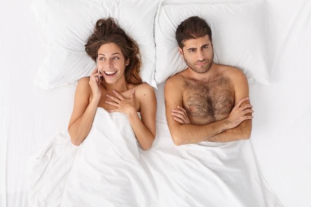 흰 담요 아래 침대에 누워있는 부부에 가까이
