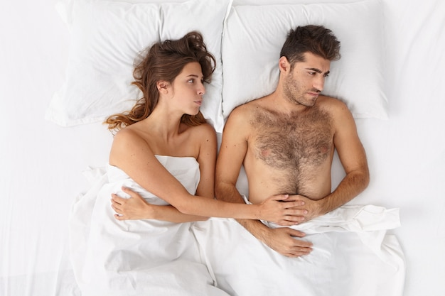 Крупным планом пара, лежа в постели под белым одеялом