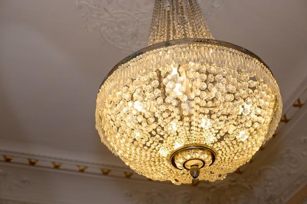 現代のシャンデリアのクリスタルにクローズアップ、天井や壁に取り付けられるように設計された分岐装飾照明器具です。ヴィンテージクリスタルランプ。コピースペース