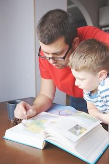 Крупный план, как папа помогает сыну изучать географию дома