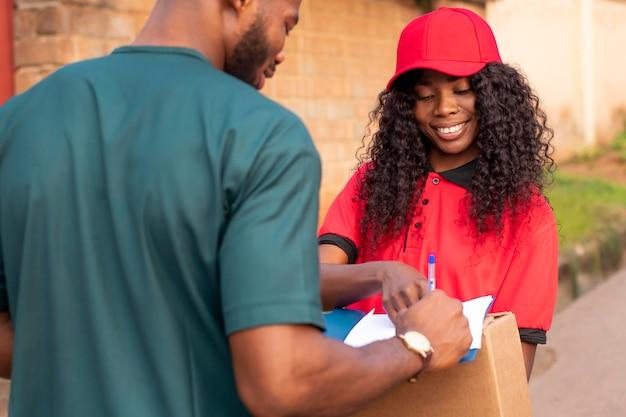 Крупным планом на доставщика, дающего посылку клиенту