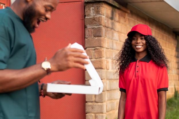 クライアントに小包を与える配達人のクローズアップ