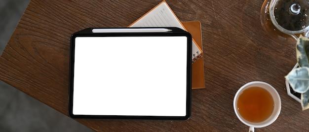Крупным планом на цифровом планшете с пустым экраном, чашкой горячего чая и записной книжкой o деревянный стол
