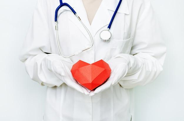 赤いハートを保持している手袋で医師の手にクローズアップ