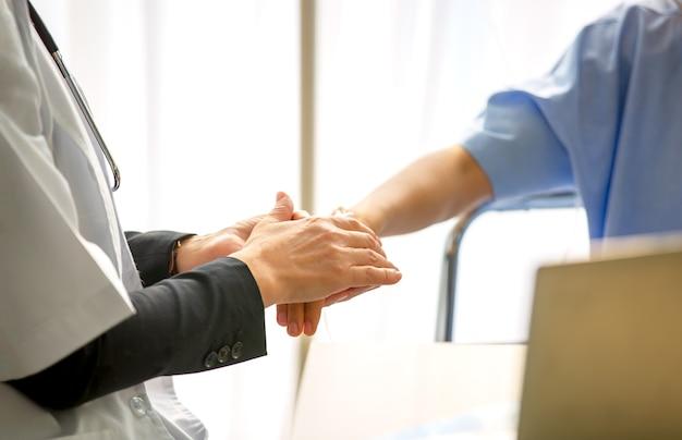 患者の手を握って医師にクローズアップ。