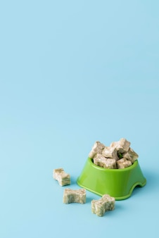 Крупным планом лакомства для собак в форме кости на миске для еды