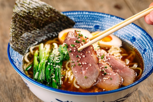 パストラミとアジタマの卵と一緒に日本のラーメンスープを食べることにクローズアップ