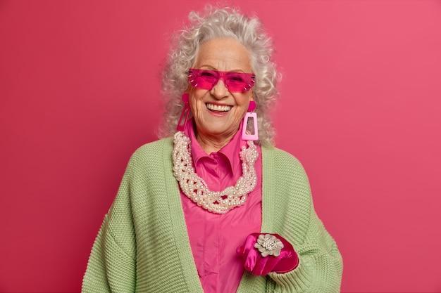 Изолированные на белом фоне элегантная пожилая женщина в стильной одежде