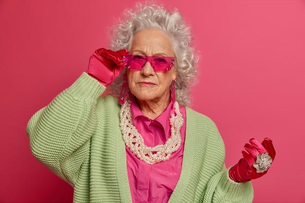 孤立したスタイリッシュな服を着てエレガントな年配の女性にクローズアップ