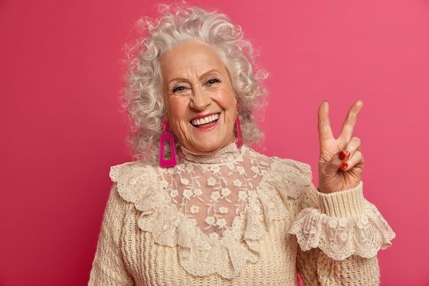 孤立したスタイリッシュな服を着てエレガントな年配の女性にクローズアップ 無料写真
