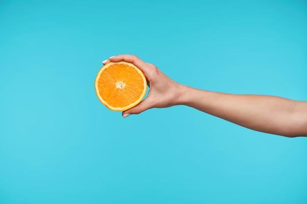 新鮮なオレンジの半分を保ちながらエレガントなかわいい手にクローズアップ