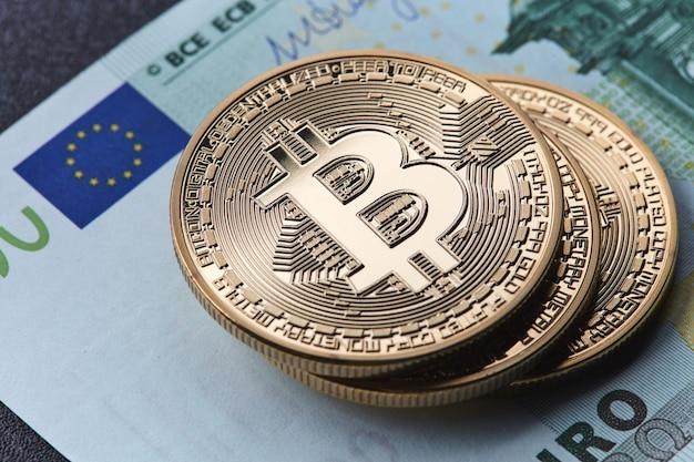 Крупным планом на банкноты евро и золотая монета биткойн